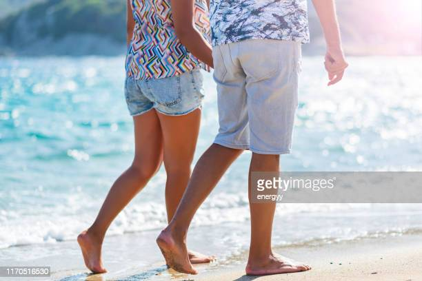 couple on a beach - denim shorts stock pictures, royalty-free photos & images