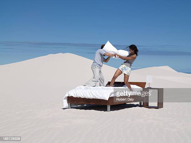 A couple on a bed having pillow fighting outdoors