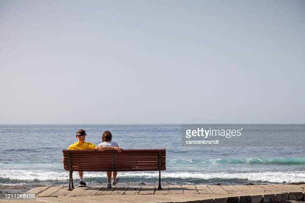 couple on a bench enjoying the view over the ocean - atlantic islands stock pictures, royalty-free photos & images