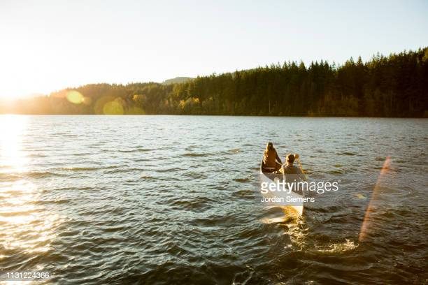 a couple on a canoe adventure - canoe stock pictures, royalty-free photos & images