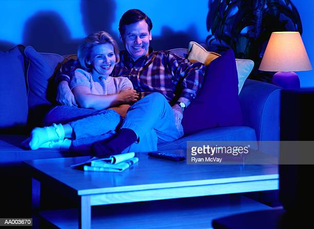 couple on a couch watching television - night in stock pictures, royalty-free photos & images