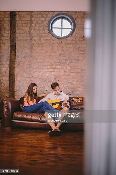Couple on a couch with the guy playing guitar