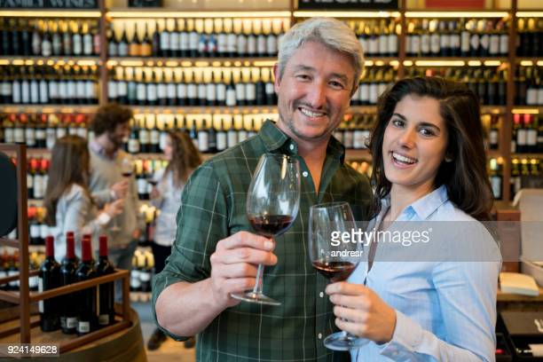 couple on a date at a winery tasting red wine and looking at camera smiling very happy - bar drink establishment stock pictures, royalty-free photos & images