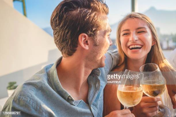 couple on a date at as restaurant. they are drinking white wine and toasting. - flirting stock pictures, royalty-free photos & images