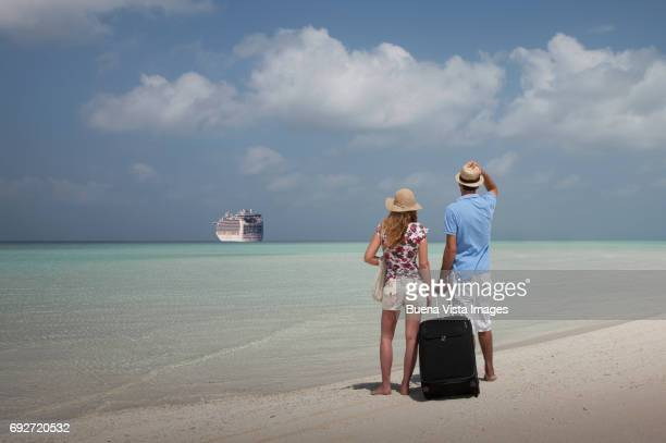 couple on a deserted island watching a leaving ship - bad luck stock pictures, royalty-free photos & images