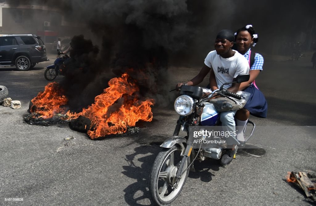 A couple on a motorcycle drive past burning tires placed by demonstrators on a main road in the Haitian capital Port-au-Prince, on September 12, 2017. Demonstrators took to the streets to protest against the government and the new budget for 2018, throwing stones at the police, setting tires on fire and blocking some streets. /