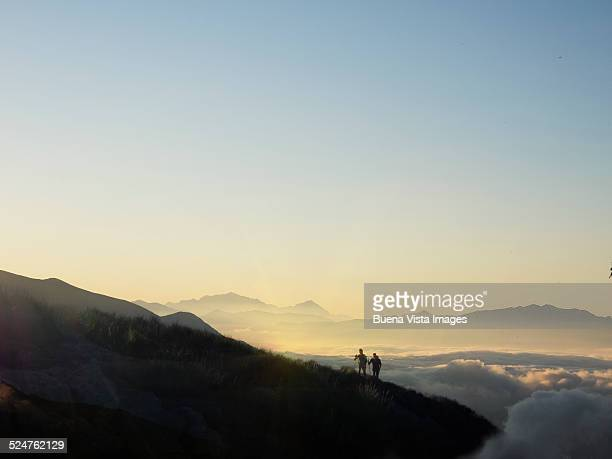 Couple on a mountain slope over fog