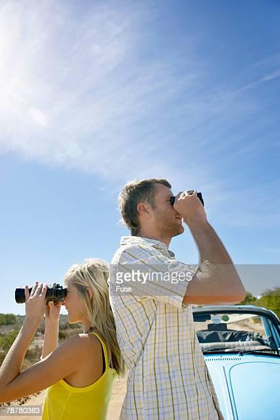 Couple on a Road Trip Looking Through Binoculars