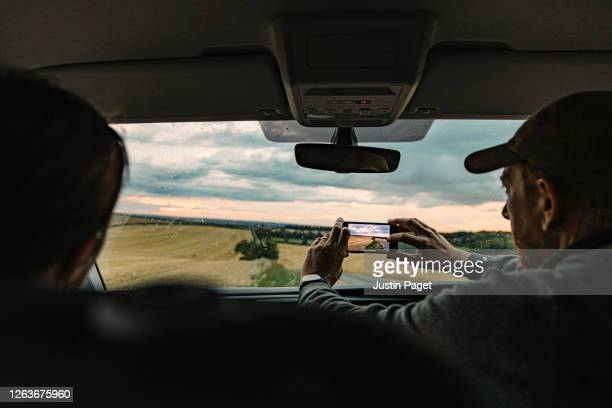 couple on a road trip. they stop to take a photo of the sunset - environment stock pictures, royalty-free photos & images