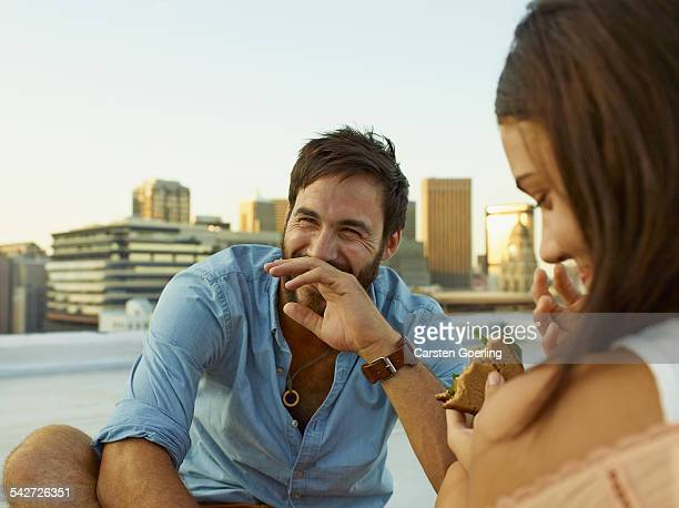 couple on a rooftop - man eating woman out stock photos and pictures