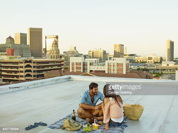 couple on a rooftop - picknick stock-fotos und bilder