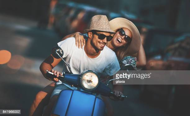 couple on a scooter bike driving through city streets. - three quarter front view stock pictures, royalty-free photos & images