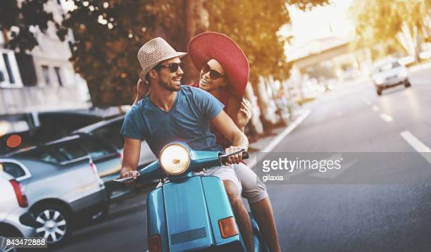 Couple on a scooter bike driving through city streets.