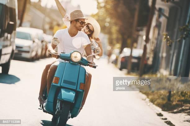 Couple sur un vélo de scooter dans les rues de la ville.