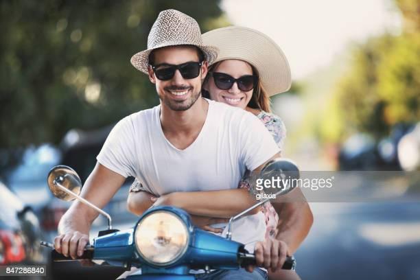 Paar auf einem Roller Fahrrad fahren durch die Straßen der Stadt.