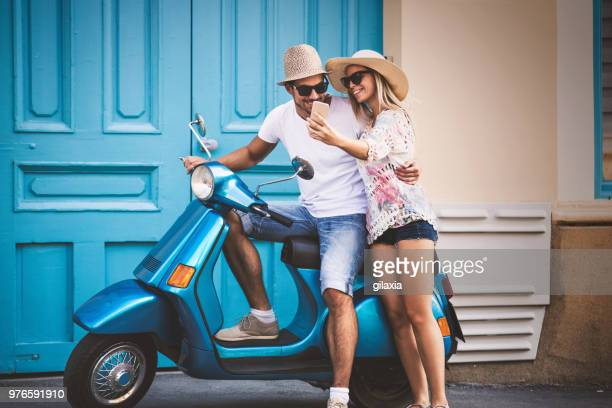 couple on a scooter bike driving through city streets. - blue shorts stock pictures, royalty-free photos & images