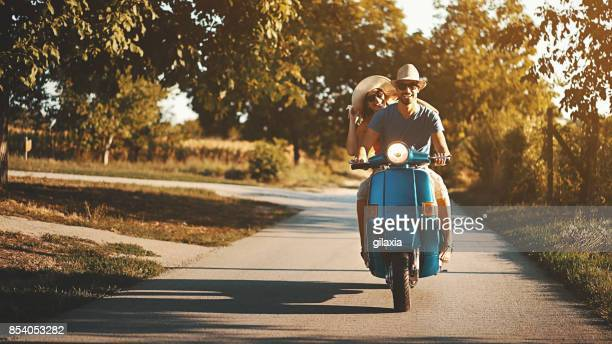 couple on a scooter bike driving through countryside. - city break stock pictures, royalty-free photos & images