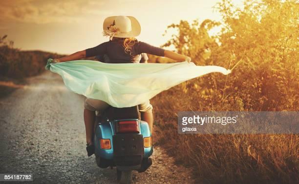Paar auf einem Roller Fahrrad fahren durch die Landschaft.