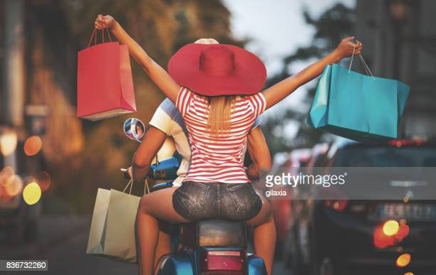 couple on a scooter coming back from shopping. - italian women stock photos and pictures
