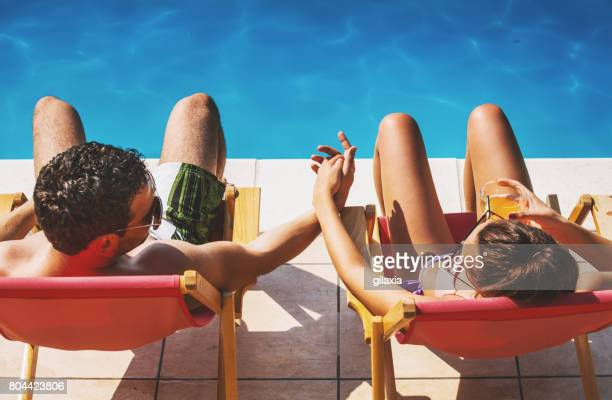 couple on a vacation. - poolside stock pictures, royalty-free photos & images