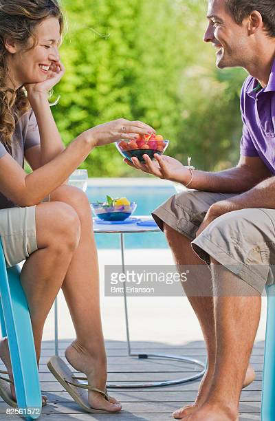 Couple on a wooden terrace by a pool