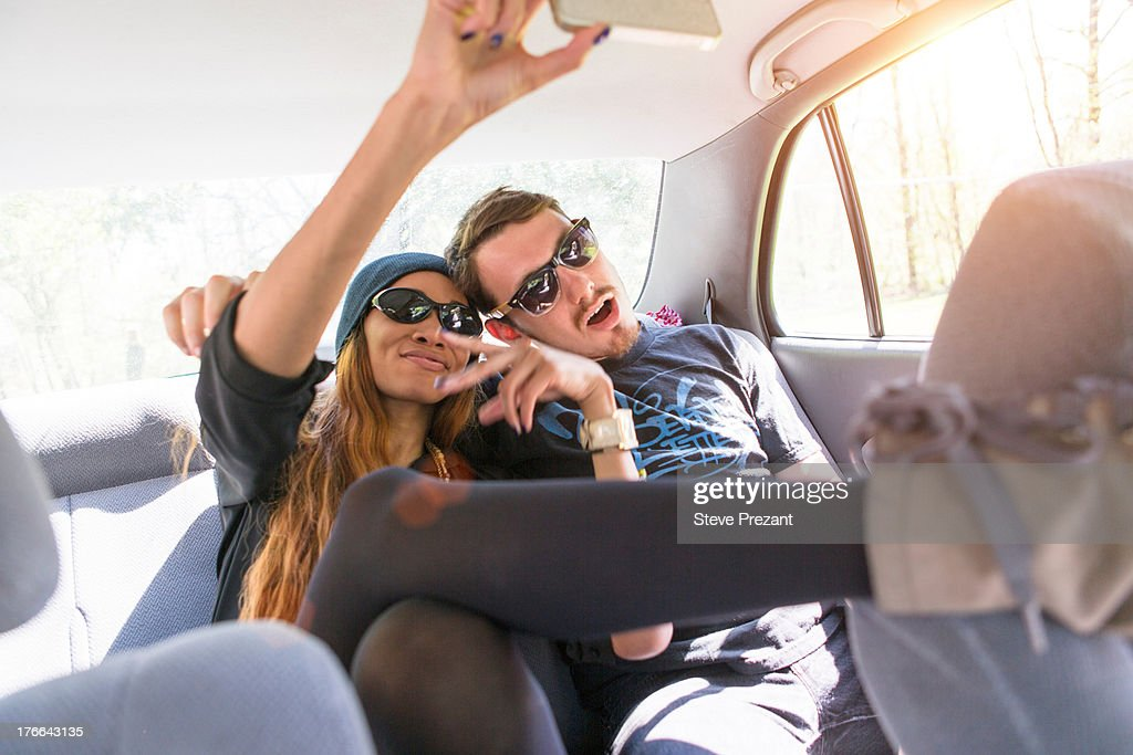 Couple on backseat in car photographing themselves : Stock Photo