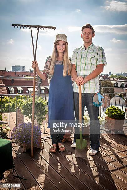 Couple On Balcony Holding Garden Rake And Shovel, Munich, Bavaria, Germany, Europe