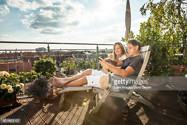 Couple On Balcony Using Mobile Phone, Munich, Bavaria, Germany, Europe