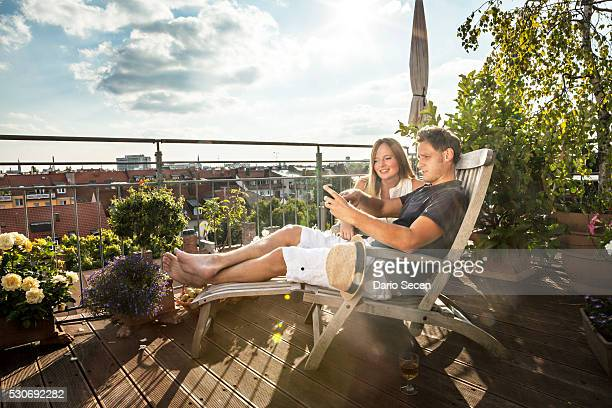 couple on balcony using mobile phone, munich, bavaria, germany, europe - balkon stock-fotos und bilder