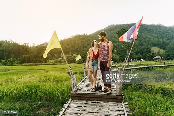 Couple on bamboo bridge in rice field