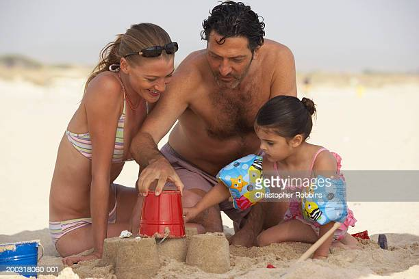 couple on beach building sandcastles with daughter (2-4) - female hairy chest stock pictures, royalty-free photos & images