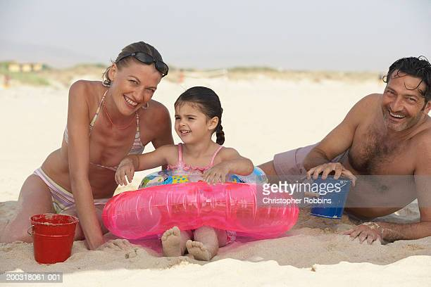 couple on beach, daughter (2-4) sitting in inflatable ring - female hairy chest stock pictures, royalty-free photos & images