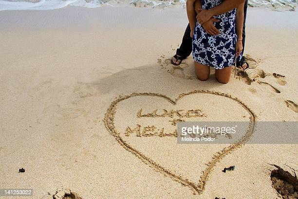 Couple on beach drawing in sand