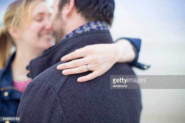 Couple on beach, embracing, womans hand showing engagement ring