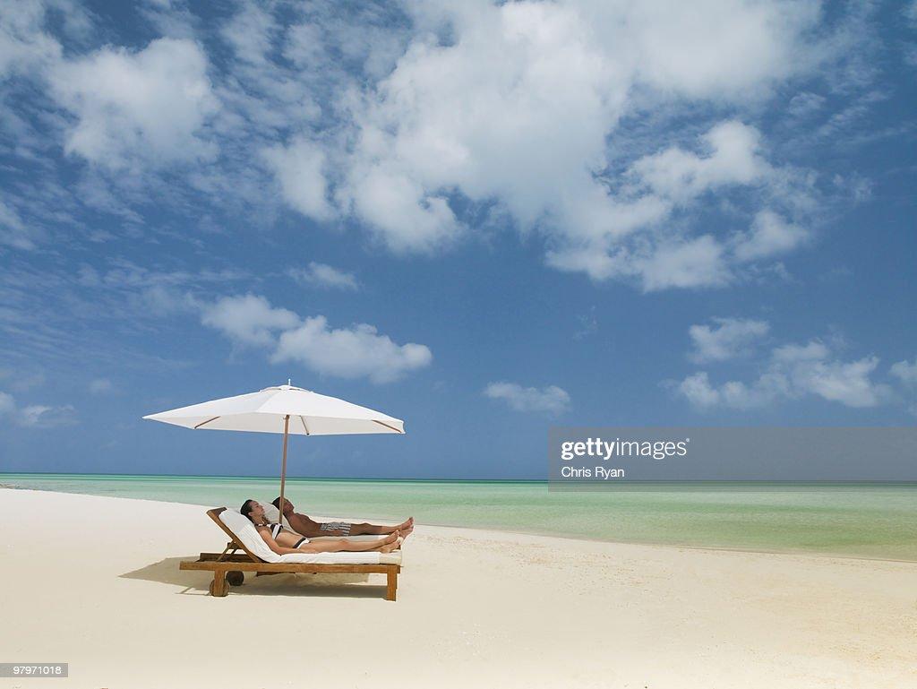 Couple on beach laying on lounge chairs under beach umbrella : Stock Photo