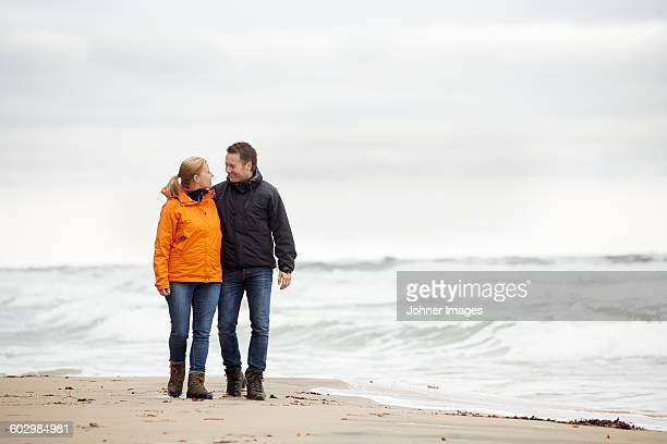 couple on beach - waterfront stock pictures, royalty-free photos & images