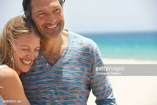 Couple on beach, smiling, close-up