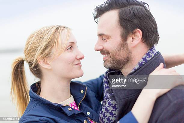 Couple on beach, smiling, face to face