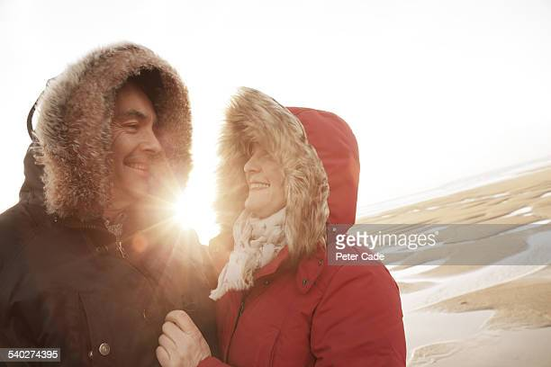 Couple on beach wearing winter coats and hats .