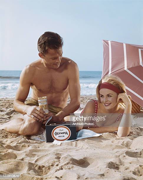 Couple on beach with drinks can, smiling
