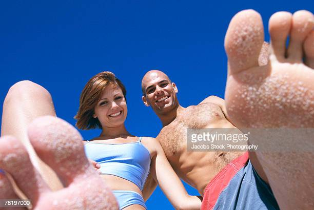 couple on beach with sand on feet - female hairy chest stock pictures, royalty-free photos & images