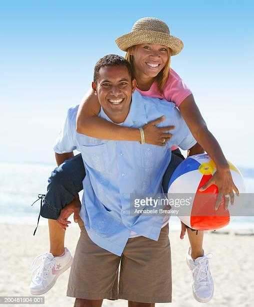 couple on beach, woman riding piggyback - heteroseksueel koppel stockfoto's en -beelden