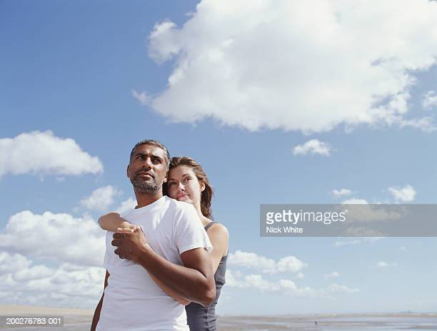 Couple on beach, woman with arms around man, low angle view