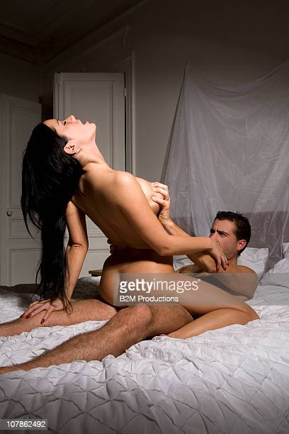 Couple on bed engaged in sexual intercourse