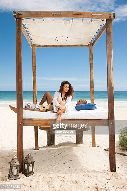 Couple on bed on sandy beach on vacation