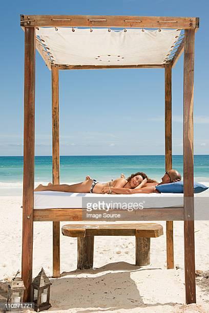 Paar auf dem Bett am Sandstrand Urlaub