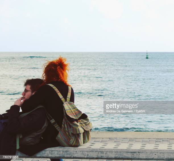Couple On Bench Against Sea