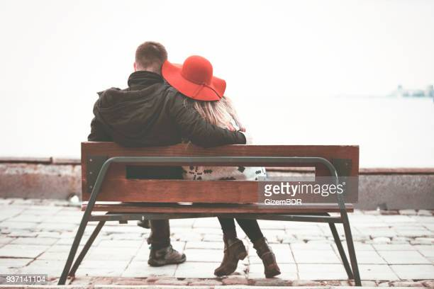 couple on bench by the lake looking at view - arm around stock pictures, royalty-free photos & images