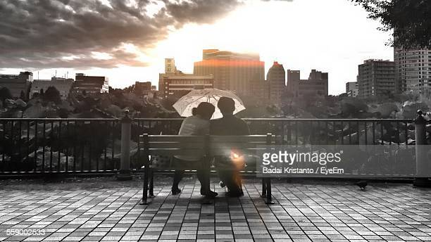 Couple On Bench With Umbrella