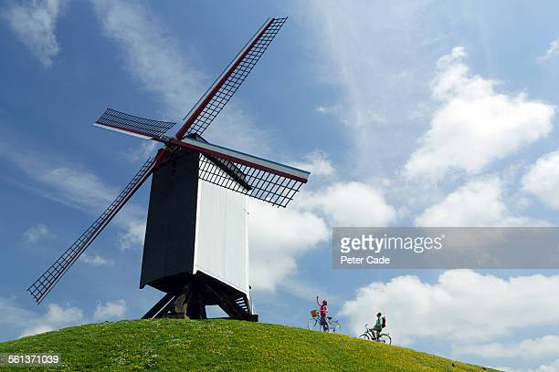 couple on bikes looking at a windmill. - フランダース ストックフォトと画像
